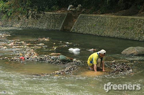 Salah satu warga mengambil pasir di dekat pintu masuk irigasi Katulampa, Bogor. Foto: greeners.co/Danny Kosasih