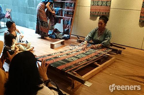 Seorang penenun asli Sikka tengah menunjukkan cara menenun kain kepada pengunjung. Foto: greeners.co/Renty Hutahaean