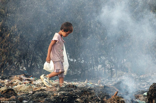 """Search"" karya Hoang Le Duy memotret seorang anak kecil yang sedang mencari barang-barang bernilai jual diantara tumpukan sampah yang terbakar. Foto: Hoang Le Duy/CIWEM Environmental Photographer of the Year"