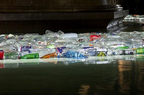 """""""Pulau Plastik"""" yang mengapung di kolam air mancur Trafalgar Square tersusun dari 13.000 botol plastik bekas. Foto: Lola Martinez/Inhabitat.com"""